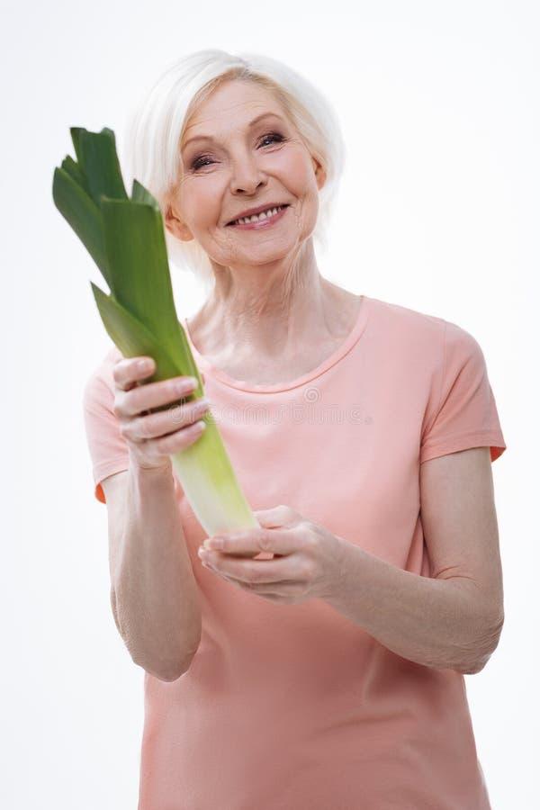 Положительный услаженный пенсионер держа лук-порей в руках стоковое фото