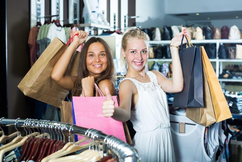 2 положительных девушки имея много хозяйственных сумок стоковые фото