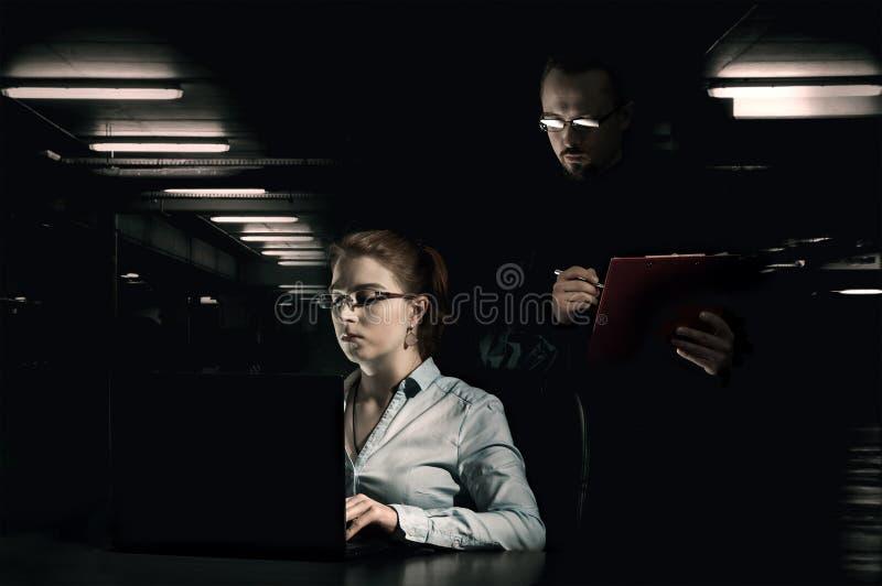 Подозрительная работа управлениями человека женщины стоковые фотографии rf