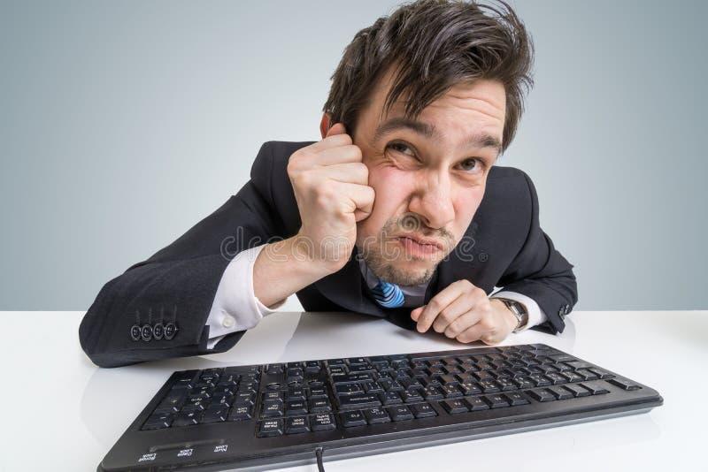 Подозрительный бизнесмен смотрит экран на работе стоковые фото