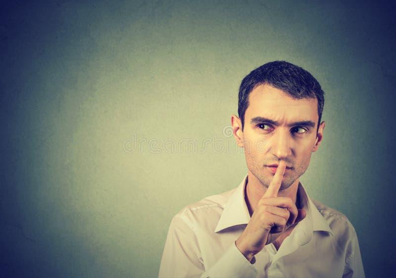Подозрительный человек давая тишь Shhhh, безмолвие, секретный жест стоковые изображения