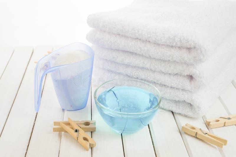 Полотенца ванны, стиральный порошок, умягчитель ткани и деревянное clothesp стоковые фото