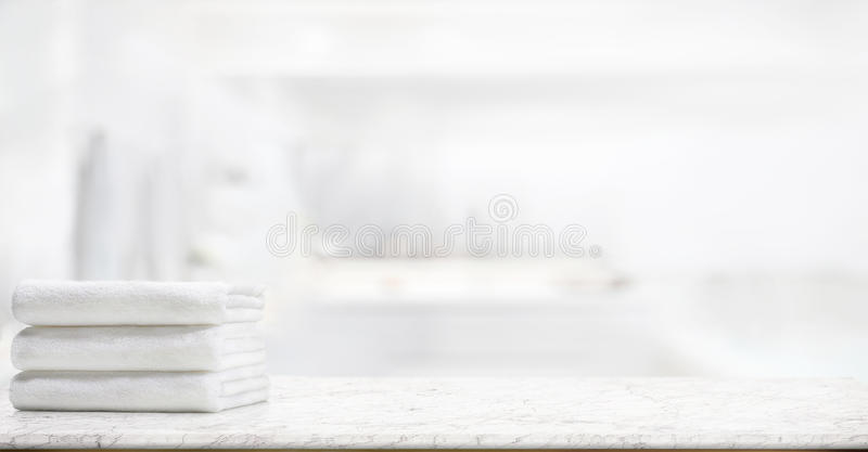 Полотенца на мраморной таблице в ванной комнате стоковое изображение