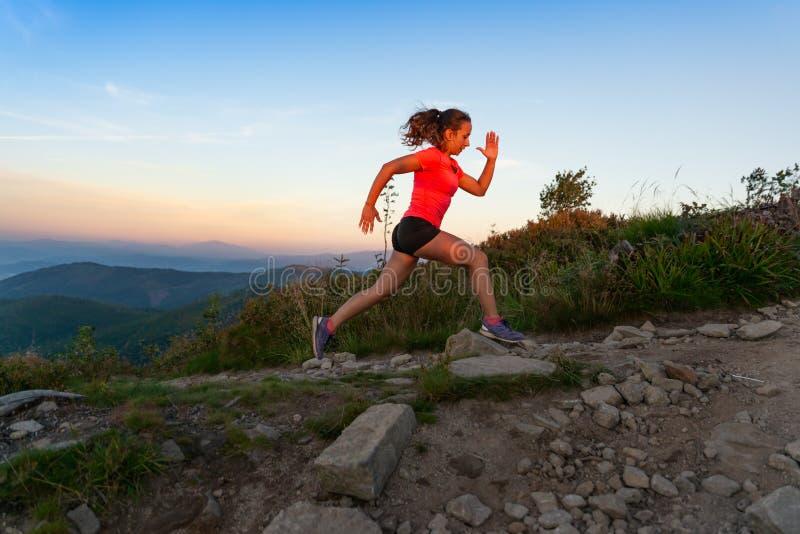 По пересеченной местности женщины бежать в горах на лете стоковое изображение rf