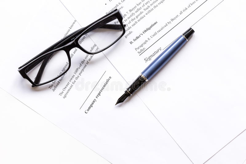 Подписывающ контракт с ручкой и стекла в деле работают взгляд сверху стоковые изображения