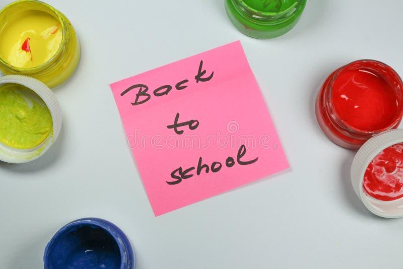 Подпишите, назад к ` школы на белой предпосылке с цветами краски стоковая фотография