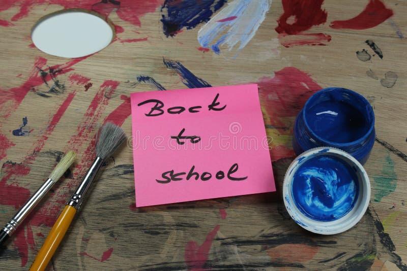 Подпишите, назад к ` школы на паллете краски с инструментами краски стоковые фотографии rf