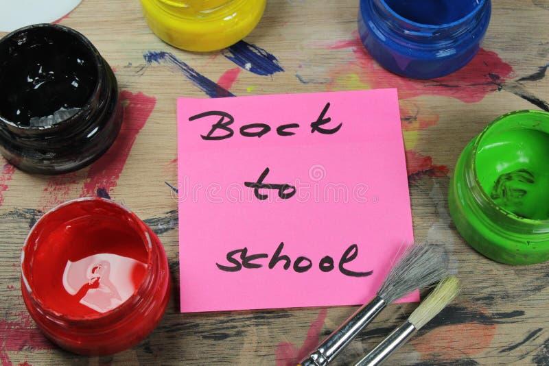 Подпишите, назад к ` школы на паллете краски с инструментами краски стоковая фотография rf