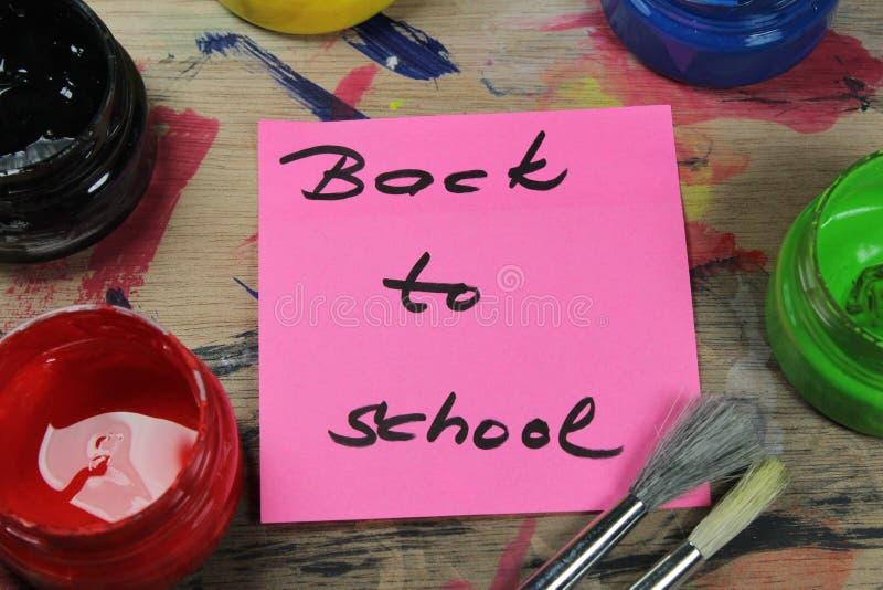 Подпишите, назад к ` школы на паллете краски с инструментами краски стоковое фото rf