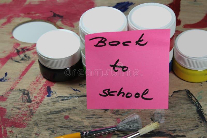 Подпишите, назад к ` школы на паллете краски с инструментами краски стоковое фото