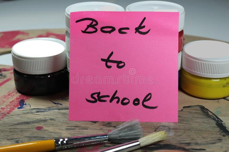 Подпишите, назад к ` школы на паллете краски с инструментами краски стоковая фотография