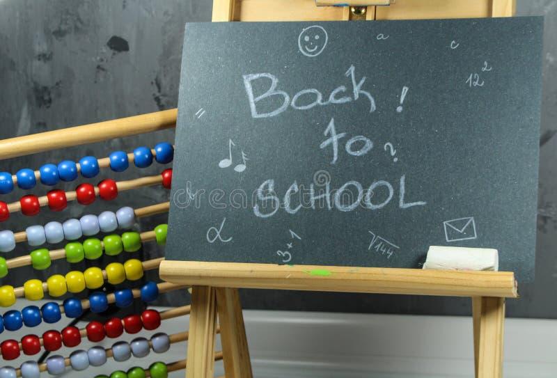 Подпишите, назад к ` школы на черной доске стоковая фотография