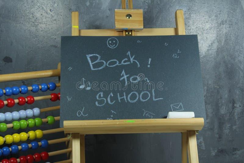 Подпишите, назад к ` школы на черной доске стоковые изображения