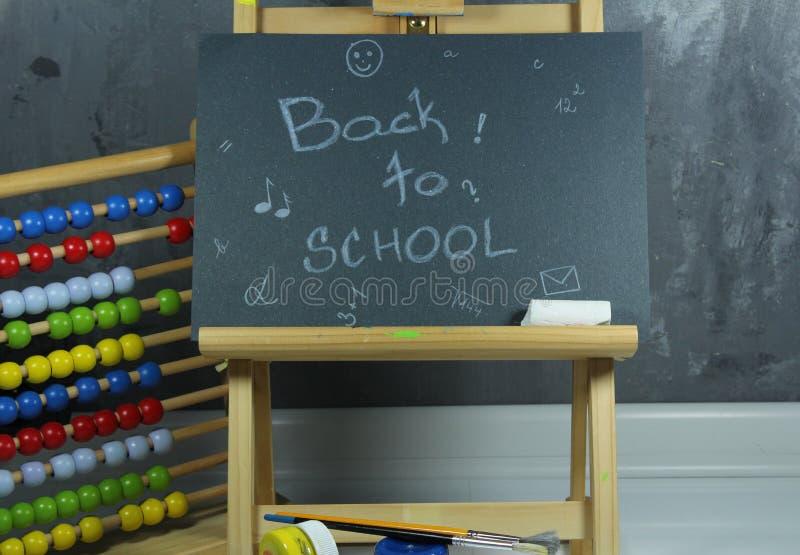 Подпишите, назад к ` школы на черной доске стоковые фото