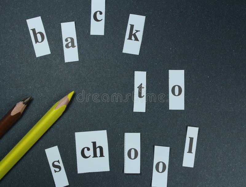 Подпишите, назад к ` школы на черной предпосылке с покрашенными карандашами стоковое фото rf
