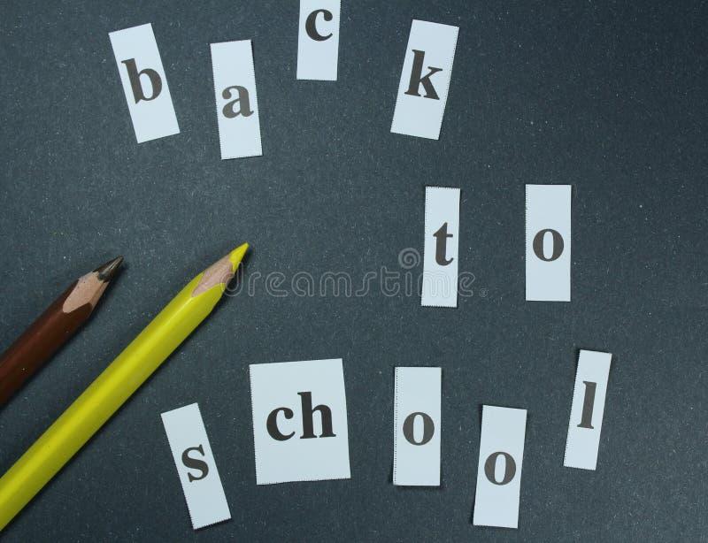 Подпишите, назад к ` школы на черной предпосылке с покрашенными карандашами стоковое фото