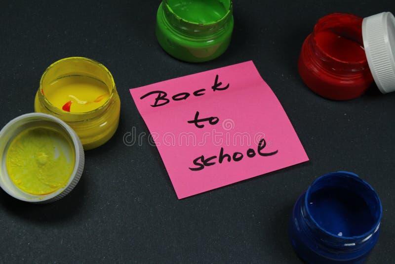 Подпишите, назад к ` школы на черной предпосылке с цветами краски стоковые изображения rf