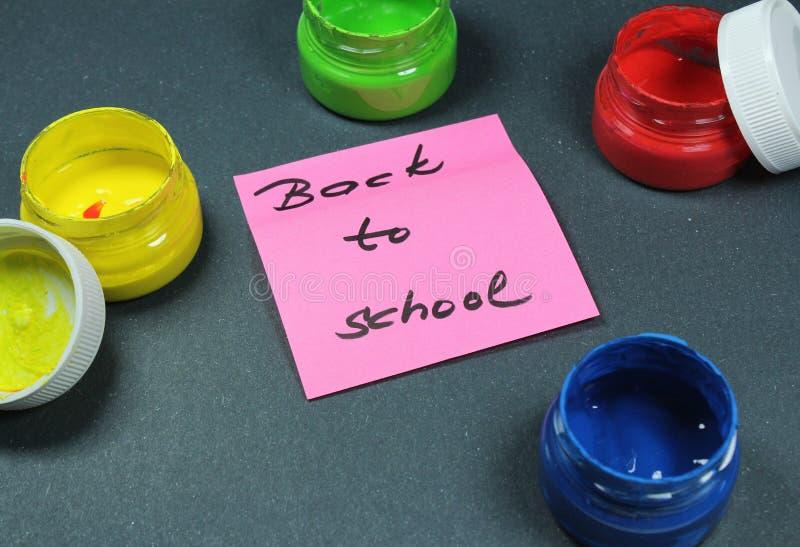Подпишите, назад к ` школы на черной предпосылке с цветами краски стоковые фото