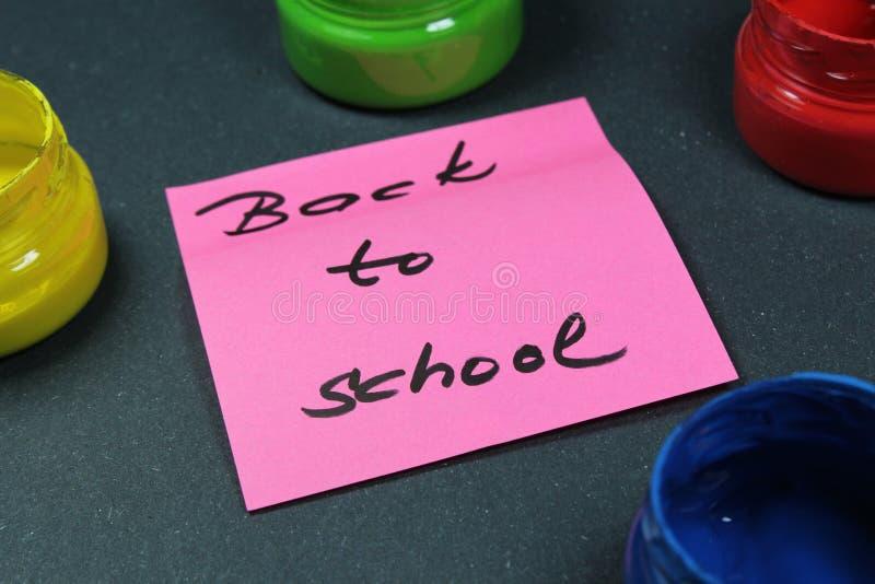 Подпишите, назад к ` школы на черной предпосылке с цветами краски стоковая фотография