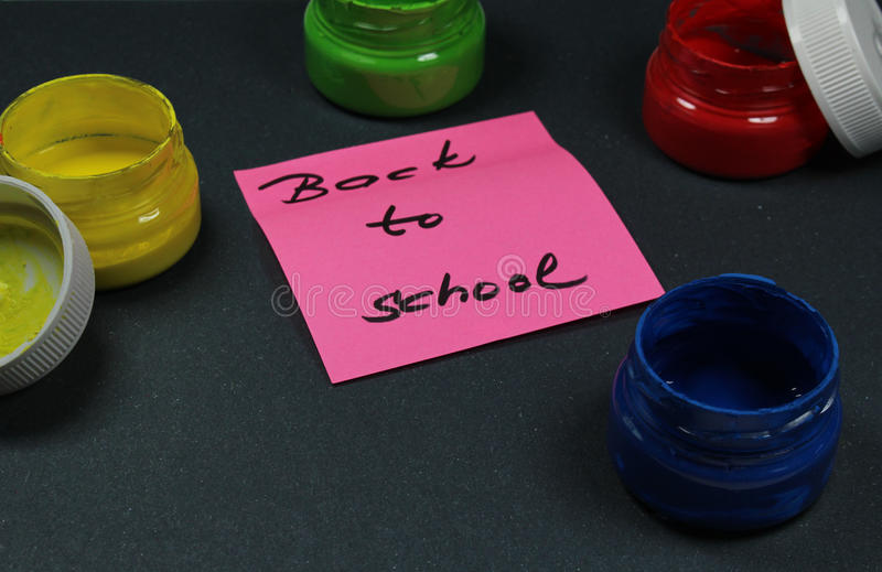 Подпишите, назад к ` школы на черной предпосылке с цветами краски стоковое фото rf