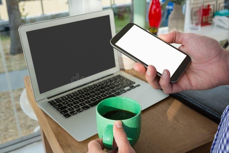 Подрезанная рука дизайнера используя умный телефон компьтер-книжкой стоковые фото