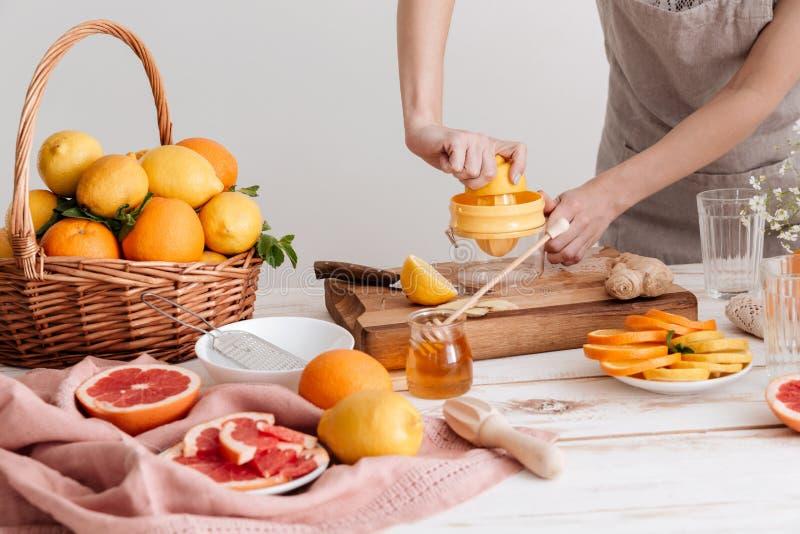Подрезанное изображение женщины сжимает вне сок цитрусы стоковое фото rf