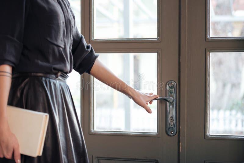 Подрезанное изображение молодой красивой дамы раскрывает дверь стоковые изображения rf