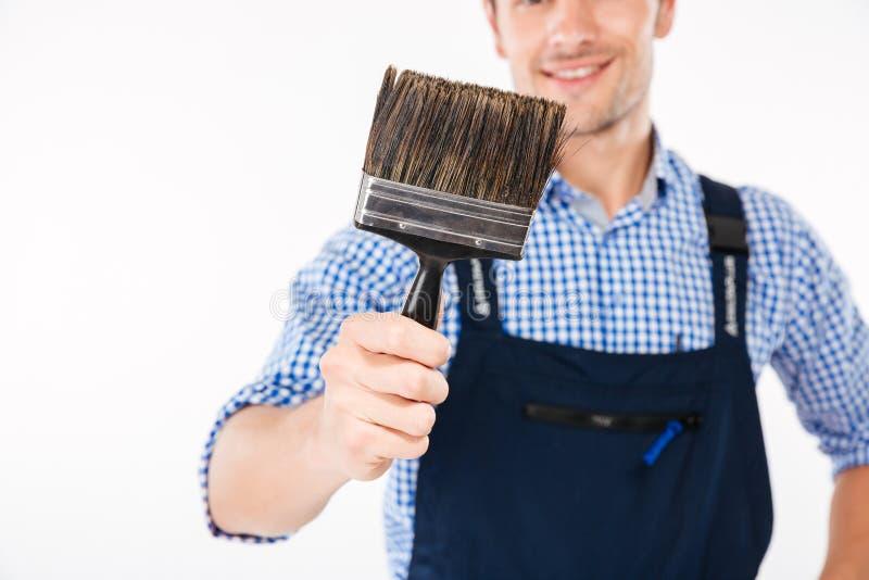 Подрезанное изображение усмехаясь мужского построителя держа кисть стоковые фото
