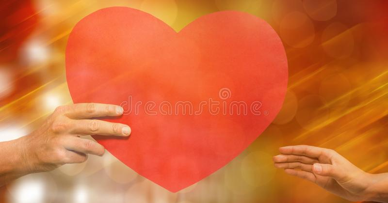 Подрезанное изображение человека давая форму сердца к женщине против bokeh стоковые фото
