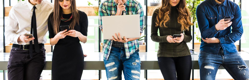 Подрезанное фото группы в составе друзья стоя на таблице и каждом польза его divices в современной комнате офиса Совместно потеха стоковые изображения