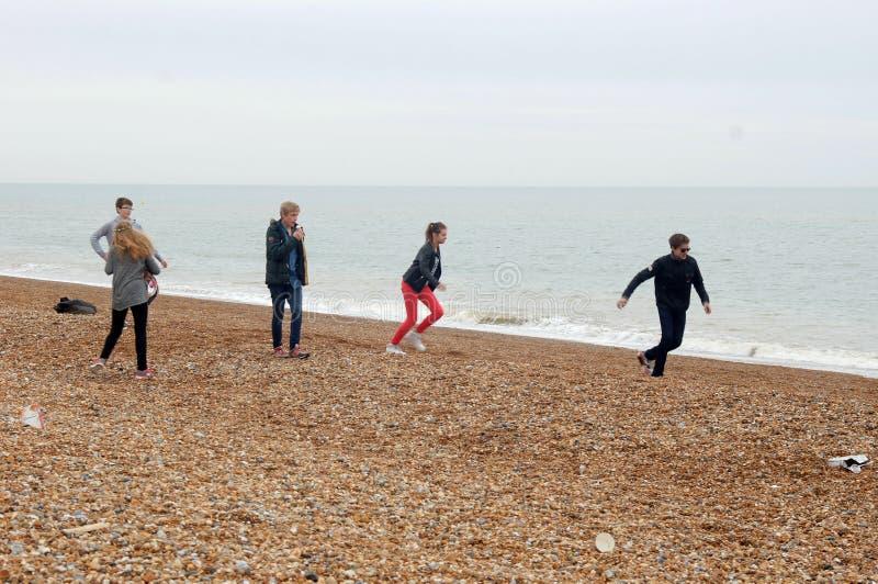 Подростки имея потеху на пляже Hastings стоковое фото rf