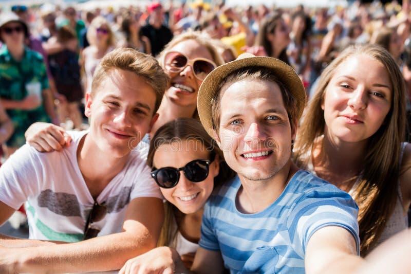 Подростки на музыкальном фестивале лета в толпе принимая selfie стоковые изображения rf