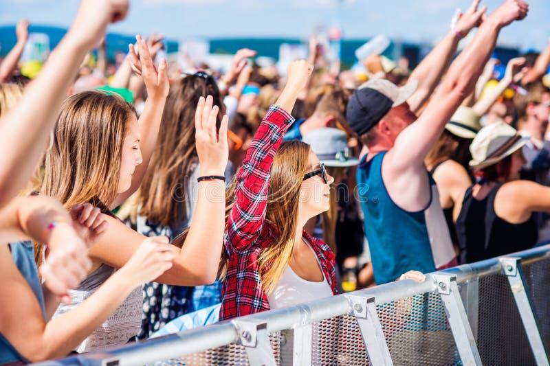 Подростки на музыкальном фестивале лета имея полезного время работы стоковые фотографии rf