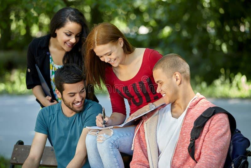 Подростки сидя на стенде и делая домашнюю работу стоковое фото