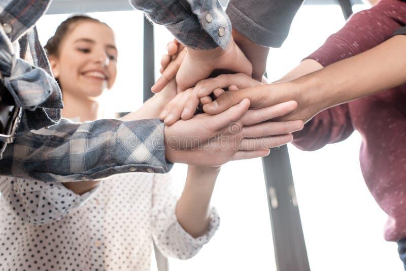 Подростки штабелируя руки совместно внутри помещения, подростки имея концепцию потехи стоковое фото rf