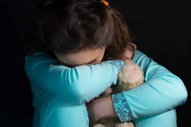 Подростковая депрессия, плача девушка держа плюшевый медвежонка стоковые фото