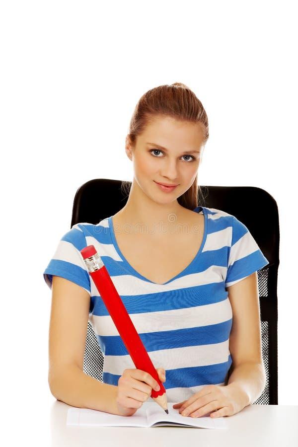Подростковая женщина делая примечания с огромной ручкой стоковые фото
