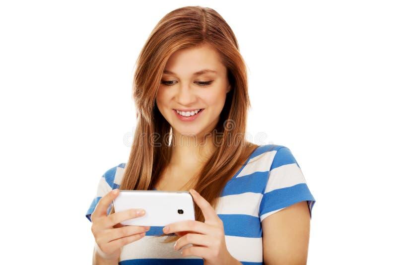 Подростковая женщина используя мобильный телефон стоковые фотографии rf