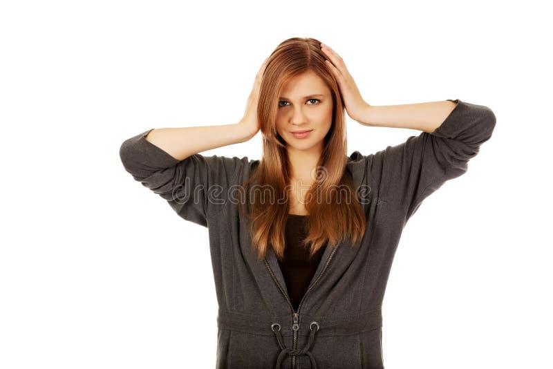 Подростковая женщина покрывая ее уши стоковое изображение