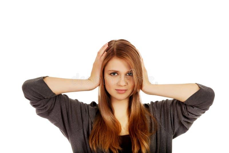 Подростковая женщина покрывая ее уши стоковые фото