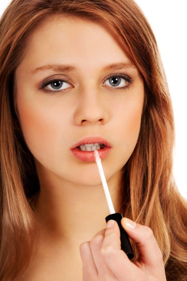 Подростковая женщина прикладывая лоск губы стоковое фото rf