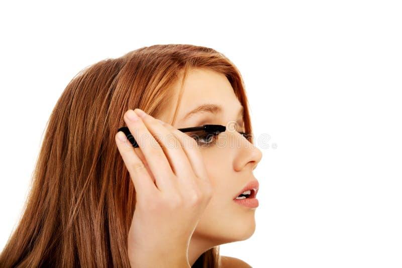Подростковая красивая женщина прикладывая тушь стоковая фотография rf