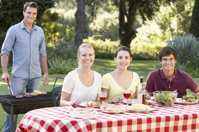 Подростковая семья наслаждаясь барбекю в саде совместно стоковое изображение rf