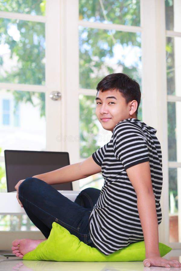 Подростковое азиатское oy используя компьтер-книжку стоковое фото
