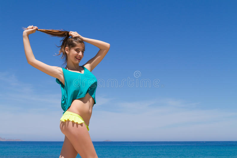 Подростковое брюнет жизнерадостное в beachwear наслаждается стоковая фотография rf