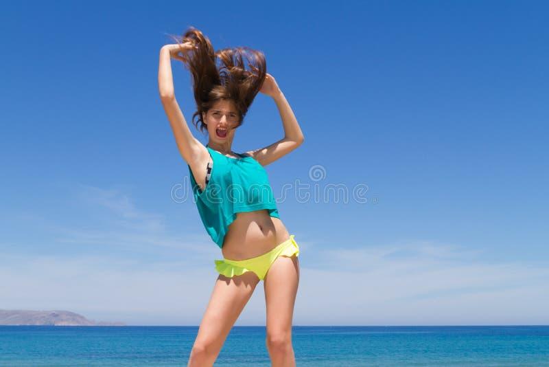 Подростковое брюнет жизнерадостное в beachwear наслаждается стоковые фотографии rf