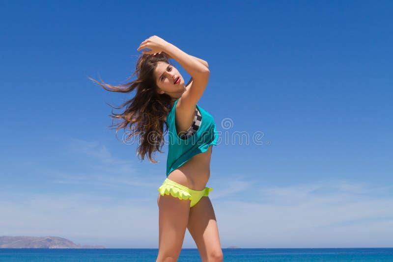 Подростковое брюнет жизнерадостное в beachwear наслаждается стоковое изображение rf