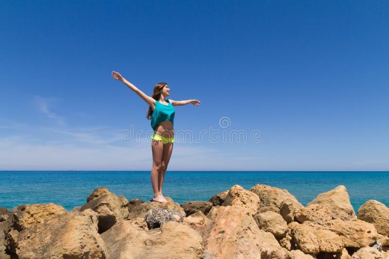 Подростковое брюнет жизнерадостное в beachwear наслаждается стоковое фото