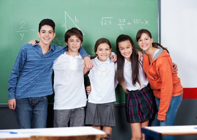 Подростковые друзья стоя совместно против доски стоковое фото rf
