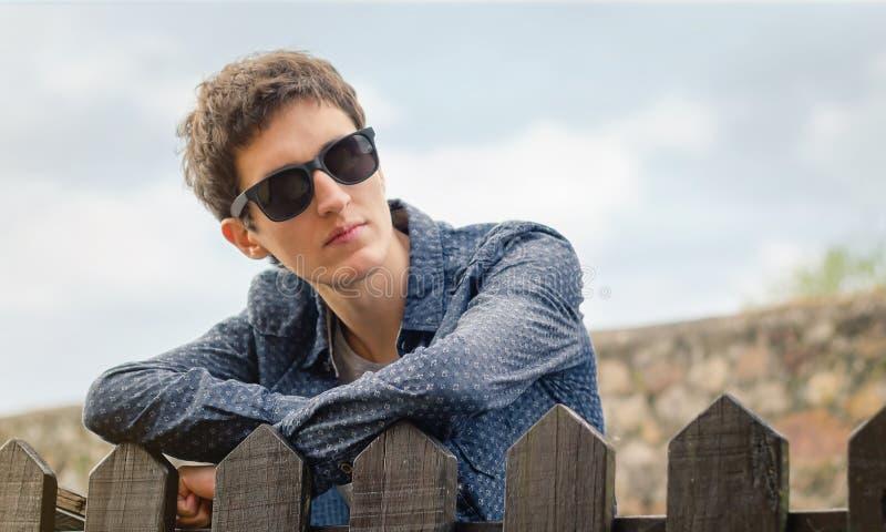Подросток битника с солнечными очками над загородкой стоковые фото